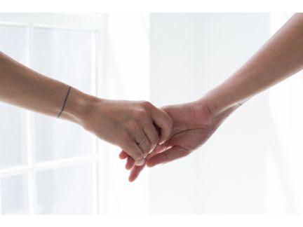 女性同士で手を繋いでいる手元の写真