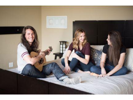 女性2人とギターを弾く男性1人
