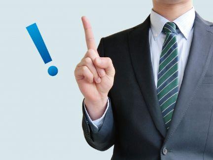 ビジネスマンが人差し指を立てポイントを示す写真