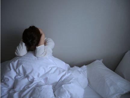 ベッドの上で頭を抱えて悩む女性