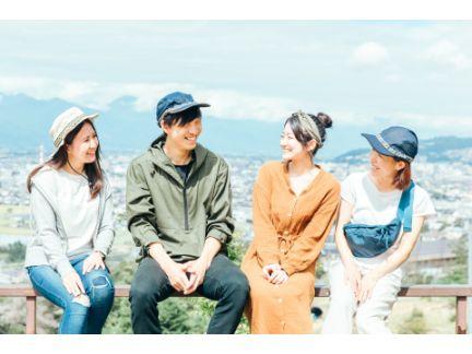 女性3人と男性1人が屋外で座って話している写真