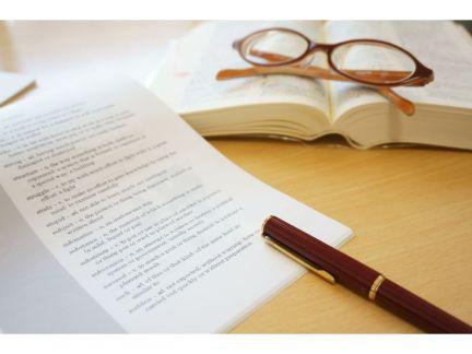 印刷された書物とペン・本と眼鏡が置いてある写真