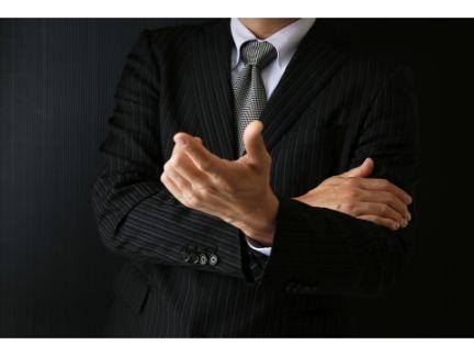 腕くみし指示を出す男性の写真