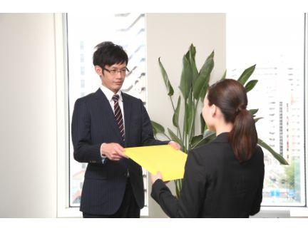 女性に書類を渡す男性の写真