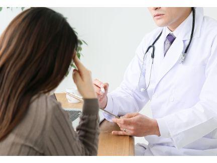 医師に悩みながら相談する女性の写真