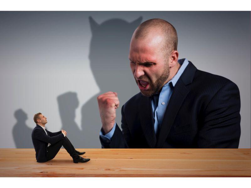 大きな上司に怒られている男性の写真
