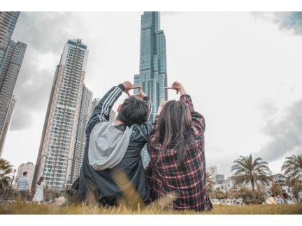 高いビルを2人で座って見る男女の写真