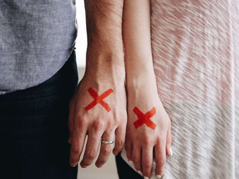 並んだカップルの手の甲に×印が書いている写真