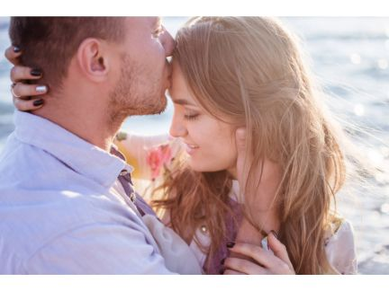男性が女性のおでこにキスする写真