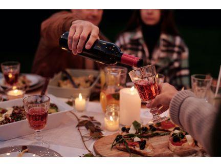 女性にワインをつぐ男性の写真