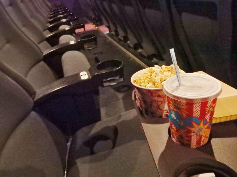 映画館の1席にポップコーンとドリンクが置いてある写真
