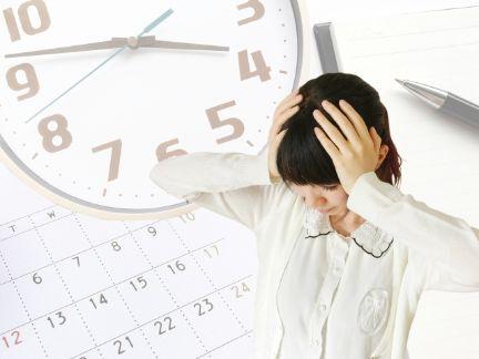 スケジュールと時計に頭を悩ます女性の写真