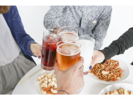 飲み会で乾杯する男女の写真