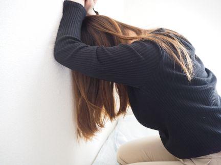 壁に手を付いて落ち込む女性の写真