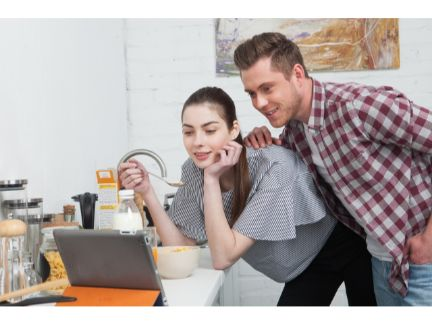 パソコンを見る仲の良い男女の写真