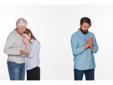 泣く母親と抱きしめる父親、少し離れている息子の写真