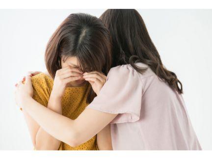 友人を慰める女性の写真