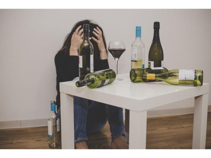 お酒をいっぱい飲んで頭を押さえる女性の写真