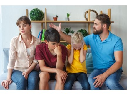 離婚話をする夫婦の間で耳を塞ぐ子供達の写真