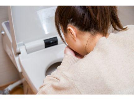 トイレで吐く女性の後ろ姿