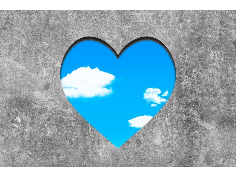 ハート型にくり抜かれた壁から青空が見える写真。