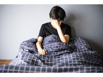 ベッドの上で眠れず悩む男性の写真