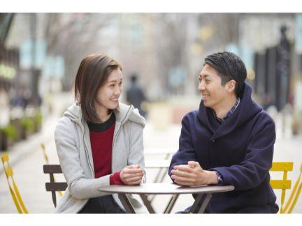 笑って話をするカップルの写真