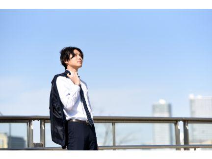 遠くの空っを見上げ黄昏る男性の写真