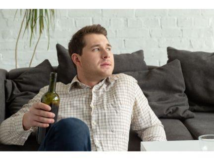 ワインを片手に物思いにふける男性の写真