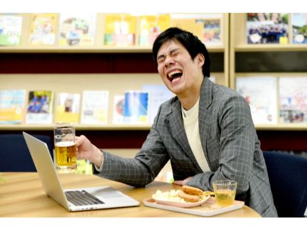 リモート飲み会で大笑いする男性の写真
