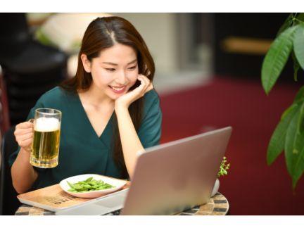 リモート飲み会でビール片手に話す女性の写真