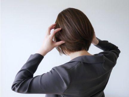 頭を押さえパニックになる女性の後ろ姿の写真