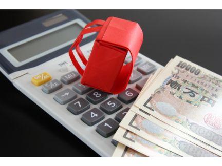 電卓の上にミニランドセルとお金の写真