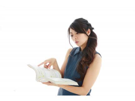 本で調べる女性の写真