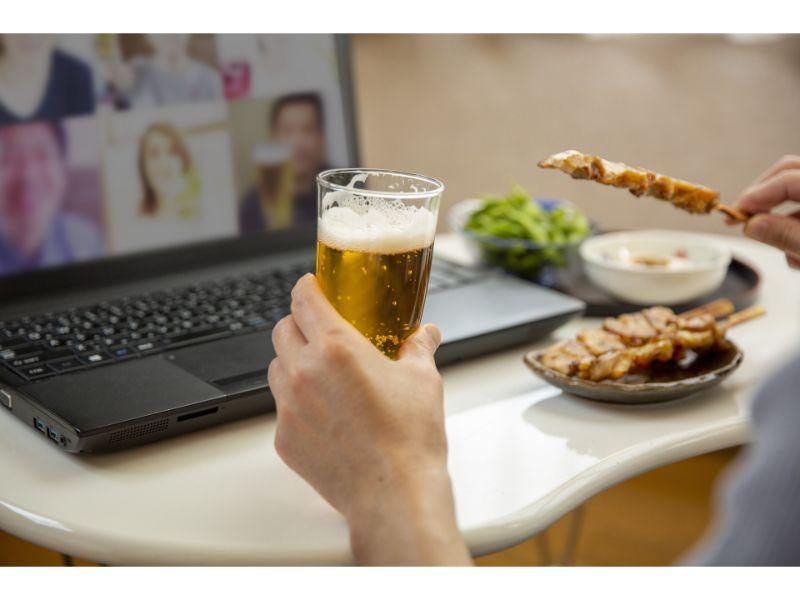 PCの前でビールと焼き鳥を持つ男性の手の写真