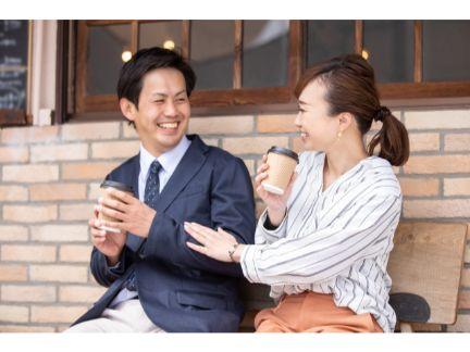 ベンチで笑い合うカップルの写真