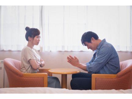 怒る女性と謝る男性の写真