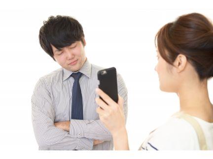 携帯を男性に見せて突き止める女性の写真