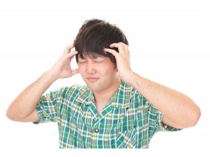 二日酔いで頭痛がしている男性の写真