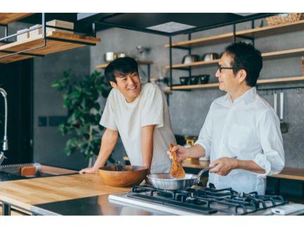 父親と息子が笑顔で料理する写真