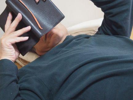 寝ながら読書をする男性の写真