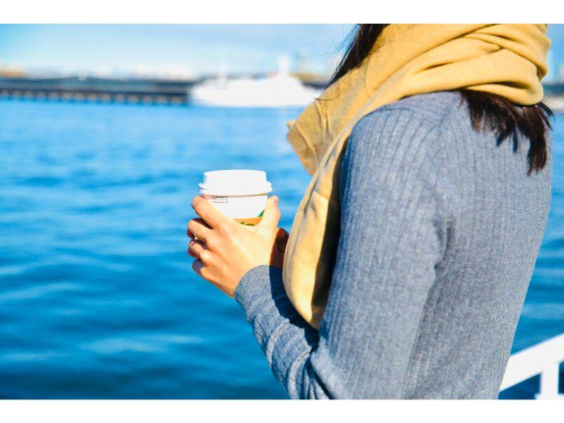 温かいコーヒーを手に持ち海を眺める女性