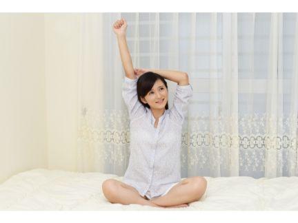 ベッドの上でストレッチする女性の写真