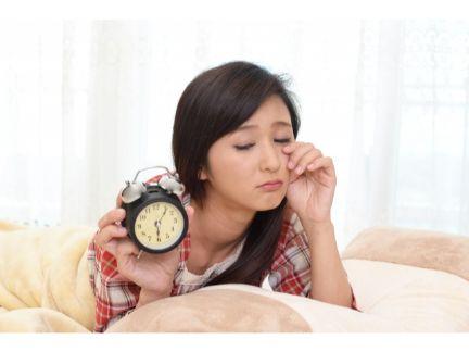 目覚まし時計を片手に眠そうな女性の写真