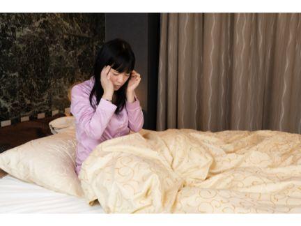 ベッドの上で頭を押さえる女性の写真