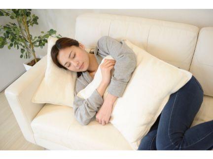 ソファーで寝る女性の写真
