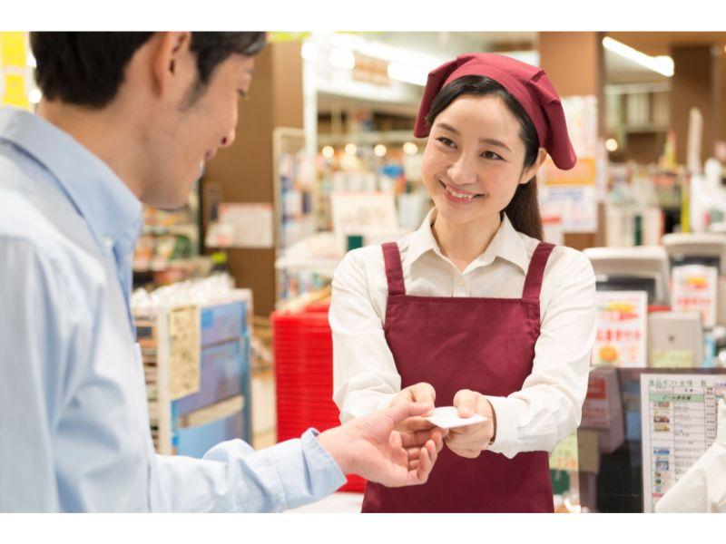 レジでレシートを渡す店員と受け取る笑顔の男性の写真