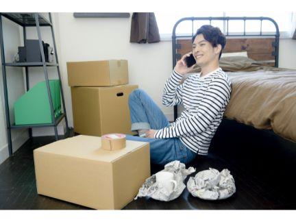 引っ越ししながら電話する男性の写真