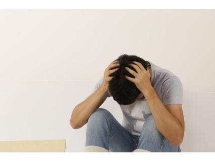 頭を抱えて悩む男性の写真