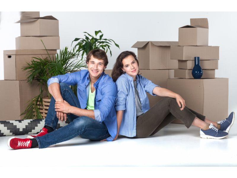 引っ越しの段ボールの前に座るカップルの写真